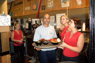 Abe Moussa with two of Abe's Mugs Grill & Bar Waitresses - Photo by Simaen Skolfield