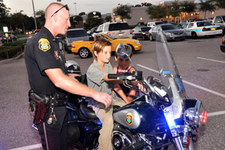 A Police Officer shows his motorcycle to local children