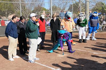 City Councilman George Cretekos, John Murphy, Chief Geer, City Manager Bill Horne, City Councilwoman Carlen Peterson and the mascots look on as Pam Ryan Anderson sweeps the plate – Photo by David Ziff