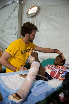 A Volunteer Minister assists a Haitian earthquake victim - Photo by Felix Kunze