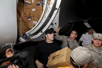 John Travolta helps deliver supplies to Haiti - Photo by Brad Kugler