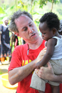 Local Clearwater businessman and Global Pioneer Cary Goulston bonds with a Haitian child. - Photo by Brad Kugler